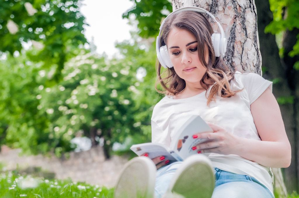 Close-up-of-young-relaxed-woman-reading-and-listening-music